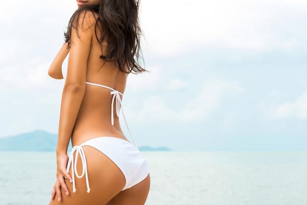 Schöne formfrau im weißen bikinibadeanzug, der am strand aufwirft