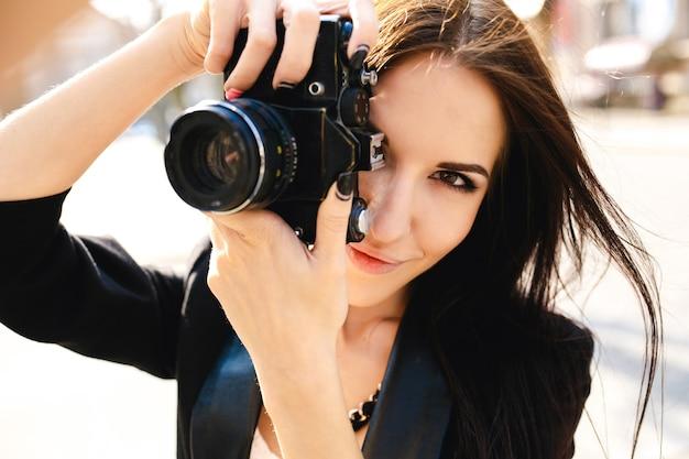 Schöne fotografin, die mit kamera aufwirft