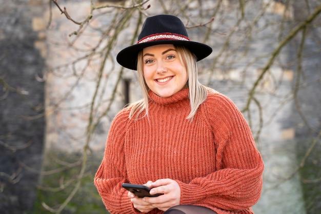 Schöne französische frau mit einem smartphone in ihren händen
