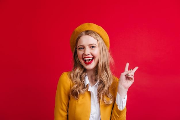 Schöne französische junge frau, die friedenszeichen zeigt. vorderansicht des gewinnenden blonden mädchens lokalisiert auf roter wand.