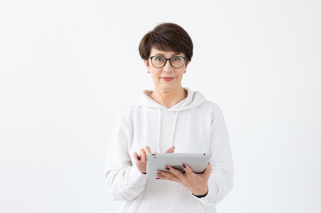 Schöne frau 50 jahre alt mit kurzen haaren, die tablette auf weißer wand mit kopienraum halten