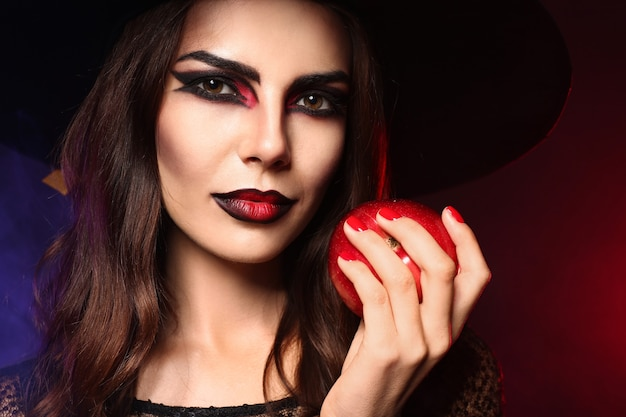 Schöne frau als hexe für halloween mit apfel auf dunkler farbe verkleidet