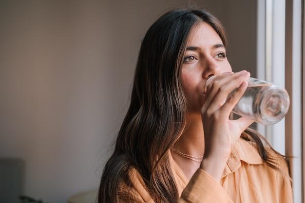 Schöne frau am fenster zu hause trinkwasser