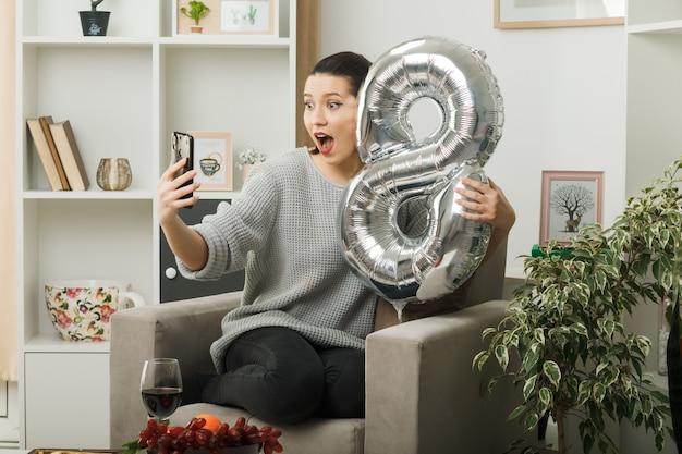 Schöne frau am glücklichen frauentag, der den ballon nummer acht hält, der auf einem sessel im wohnzimmer sitzt