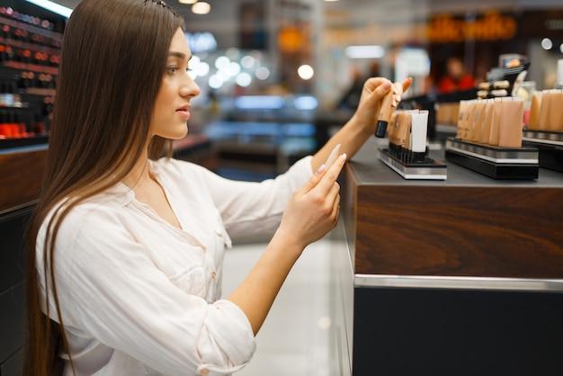 Schöne frau am regal im kosmetikladen, seitenansicht. käufer an der vitrine im luxus-beauty-shop-salon, kundin im modemarkt