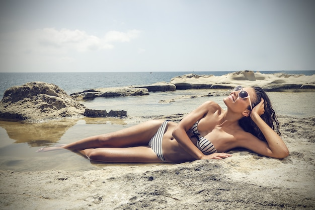 Schöne frau am strand liegen