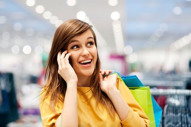 Schöne frau am telefon im einkaufszentrum