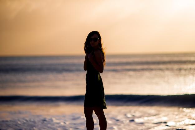 Schöne frau am weißen strand bei sonnenuntergang.