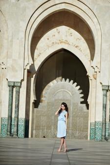 Schöne frau auf dem hintergrund der moschee in casablanca marokko