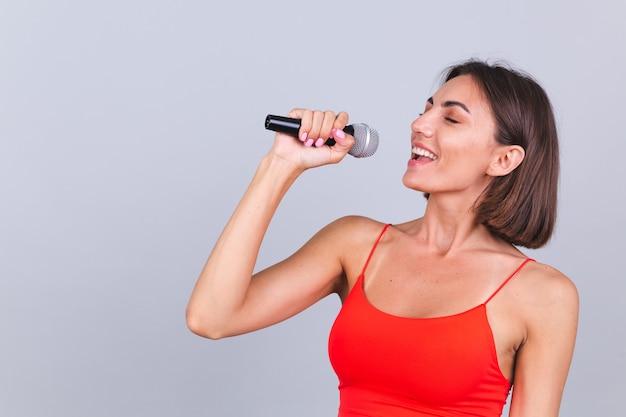 Schöne frau auf grauer wand mit mikrofon singt emotionales lieblingslied fröhlich positiv fröhlich