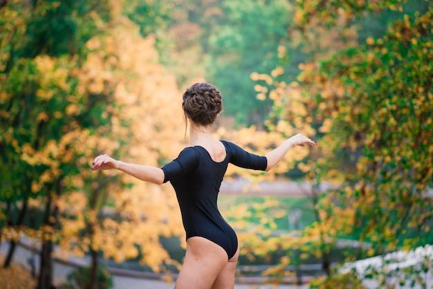 Schöne frau, ballerina, athlet im schwarzen bodysuit-training im park