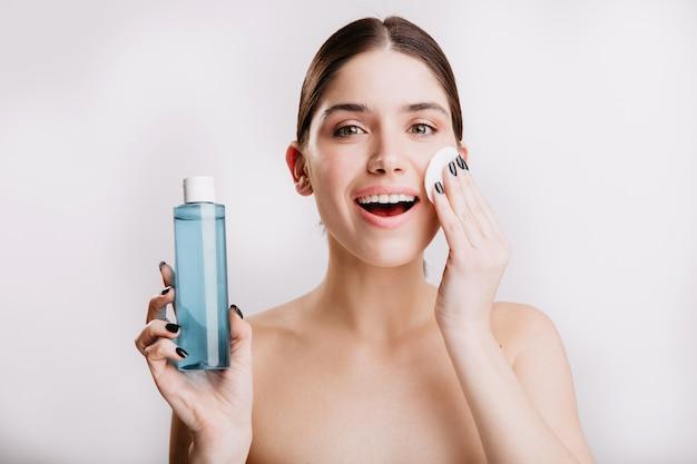 Schöne frau befeuchtet zart haut mit kosmetischem tonikum. porträt der dame mit gesunder haut ohne make-up auf isolierter wand.