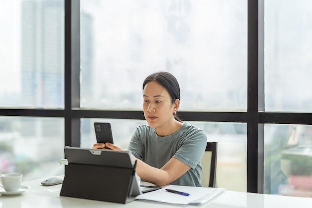 Schöne frau bei einem videoanruf auf ihrem handy, während sie im büro arbeitet