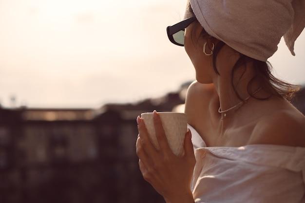 Schöne frau bei sonnenuntergang tee trinken auf dem balkon