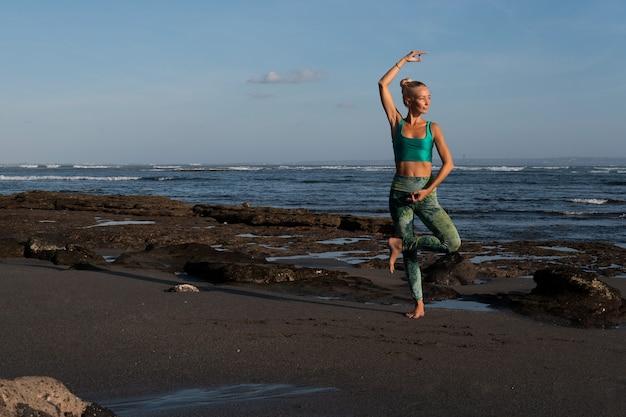 Schöne frau beim yoga am strand