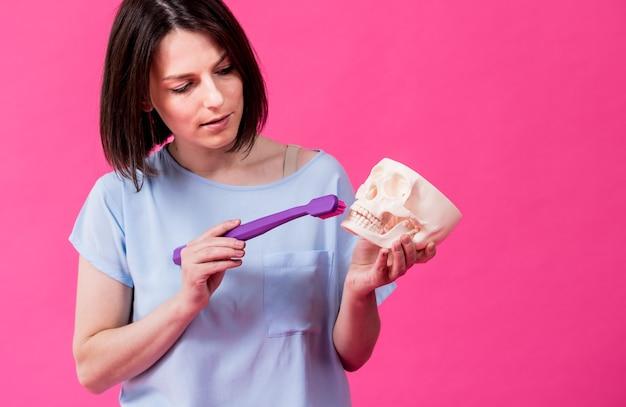 Schöne frau beim zähneputzen eines künstlichen schädels mit einer großen zahnbürste