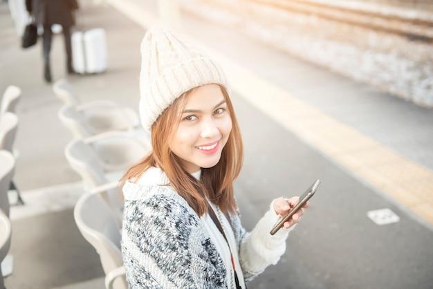 Schöne frau benutzt intelligentes telefon auf bahnsteig
