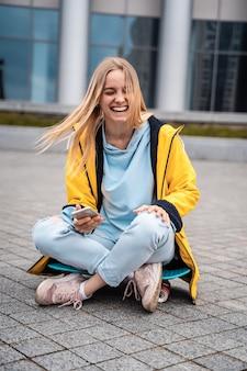 Schöne frau benutzt smartphone und sitzt auf skateboard