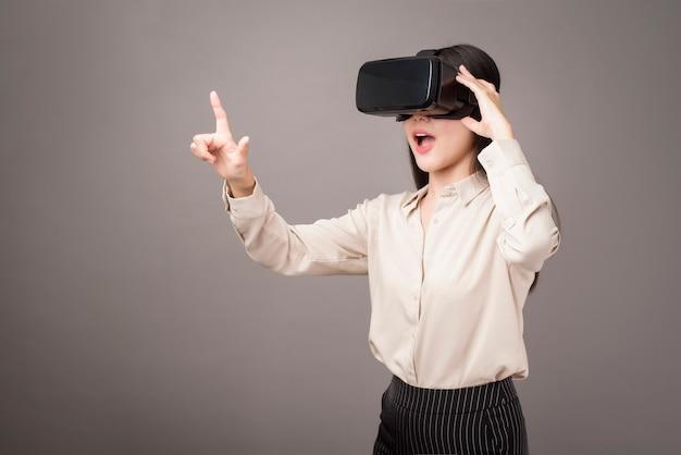 Schöne frau benutzt virtuelle realität auf grau