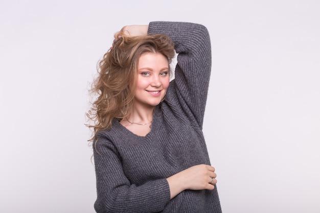 Schöne frau berührt ihr lockiges haar auf weißem hintergrund