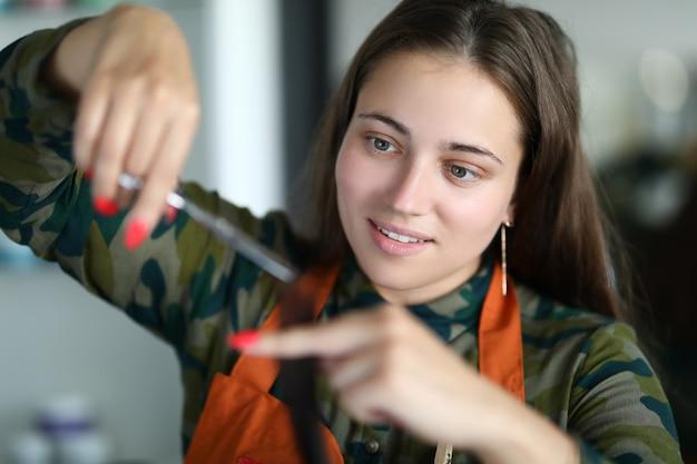 Schöne frau blick auf haarlocke nahaufnahme. professioneller friseur schneidet haare beim friseur. service zur schaffung eines neuen images von menschen. transformation und aussehen verändern sich im schönheitssalon.