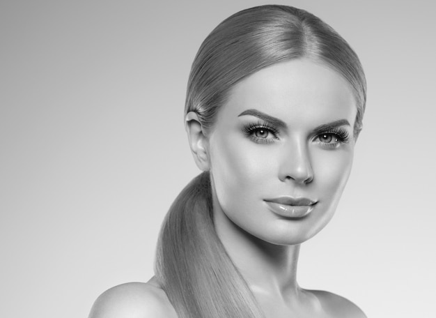 Schöne frau blond mit natürlichem make-up des langen haares und gesundem hautkosmetikkonzept. studioaufnahme. einfarbig. grau. schwarz und weiß. studioaufnahme.