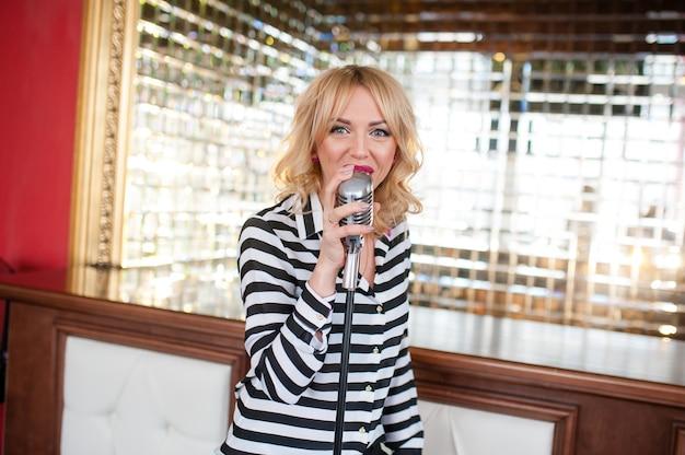 Schöne frau, blondine, mikrofon. gesang, schönes lächeln