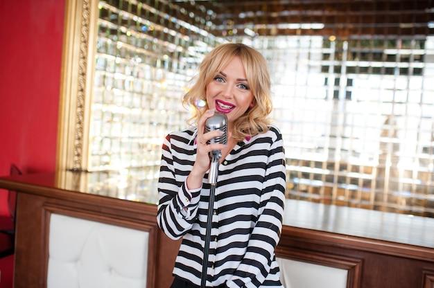 Schöne frau, blondine, mikrofon singend, schönes lächeln