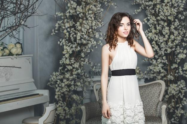 Schöne frau braut in einem weißen kleid gegen vintage weißen frühling interieur