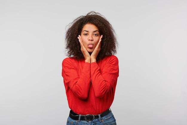 Schöne frau der hübschen frau, jung, süß im roten langarm mit langer afro-frisur zeigt zunge