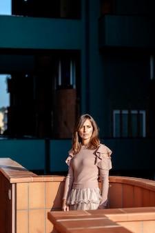 Schöne frau der mittleren erwachsenen, die sich auf balkon in einem modernen gebäude stützt