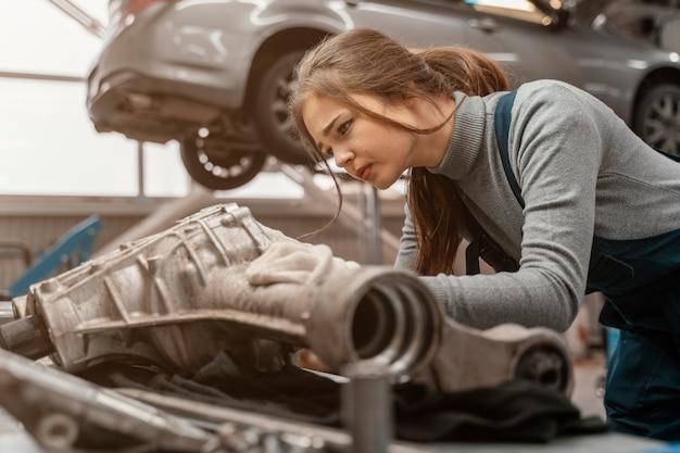 Schöne frau der seitenansicht, die an einem autoservice arbeitet