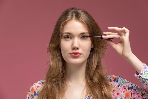 Schöne frau der vorderansicht, die make-up-zubehör für ihre augen verwendet