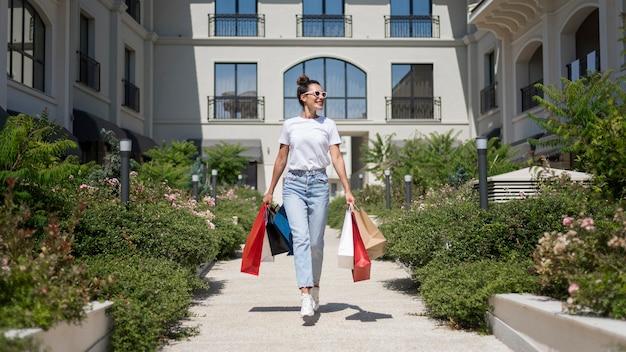 Schöne frau der vorderansicht, die mit einkaufstaschen aufwirft