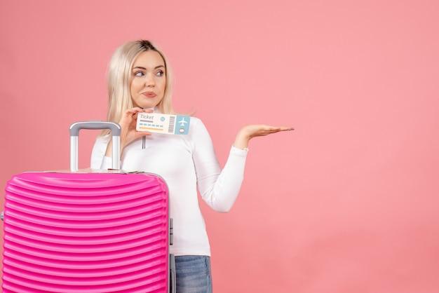 Schöne frau der vorderansicht mit rosa koffer, der flugticket hält
