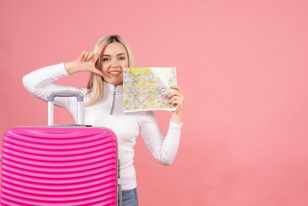 Schöne frau der vorderansicht mit rosa koffer, der verliererzeichen hält karte hält