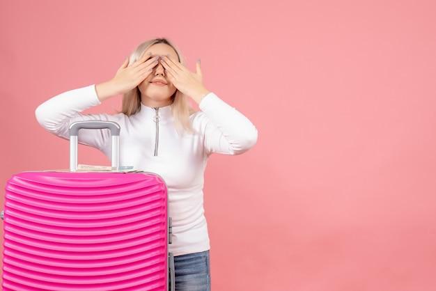 Schöne frau der vorderansicht mit rosa koffer, die hände auf ihre augen setzen