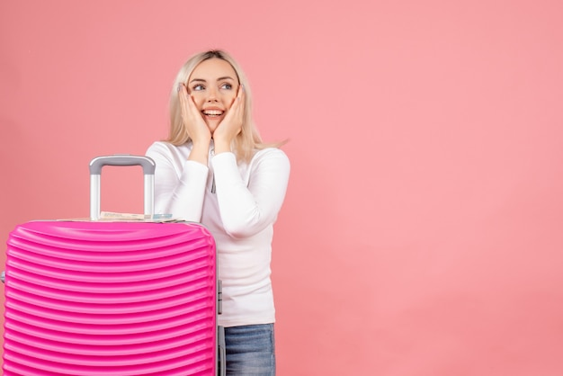 Schöne frau der vorderansicht mit rosa koffer, die hände auf ihre wange setzen