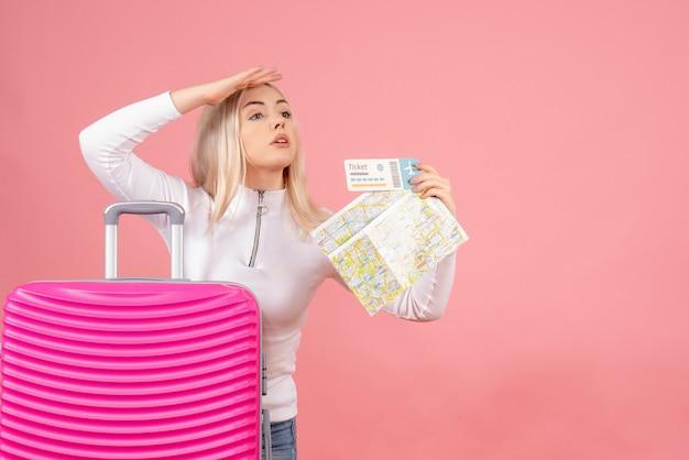 Schöne frau der vorderansicht mit rosa koffer, die karte und ticket hält