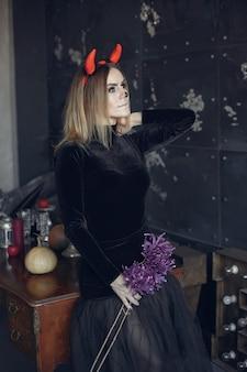 Schöne frau des halloween-schminkens mit blonder frisur. modell mädchen im schwarzen kostüm. halloween-thema.