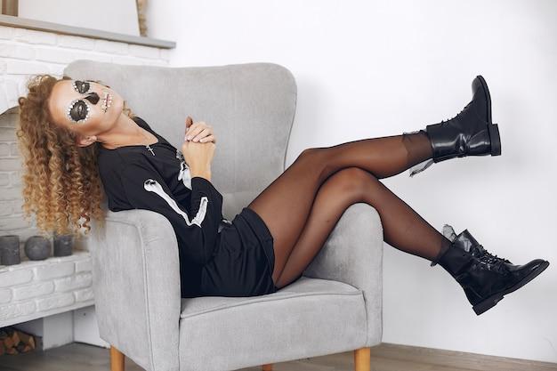 Schöne frau des halloween-schminkschädels mit blonder frisur. santa muerte model girl im schwarzen kostüm.