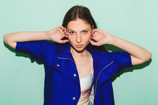 Schöne frau des jungen hipsters, blau posierend gegen blaue wand, badeanzug-modetrend sommer, kühler gesichtsausdruck