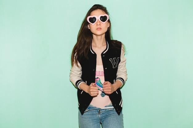 Schöne frau des jungen hipsters, lustige herzsonnenbrille, gegen blaue wand, kühler gesichtsausdruck