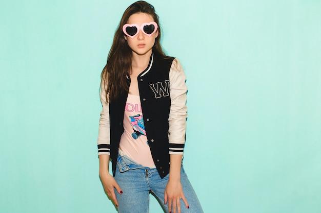 Schöne frau des jungen hipsters, lustige herzsonnenbrille, gegen blaue wand, nicht isoliert, kühler gesichtsausdruck