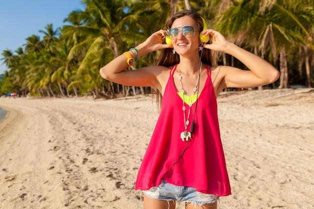 Schöne frau des jungen hipsters, tropischer strand, urlaub, bunt, sommertrendstil, sonnenbrille, kopfhörer, musik hören, palmenhintergrund, glücklich lächelnd, spaß, details, nahaufnahmeporträt