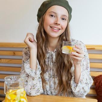 Schöne frau des mittleren schusses, die am tisch sitzt und limonadenglas hält