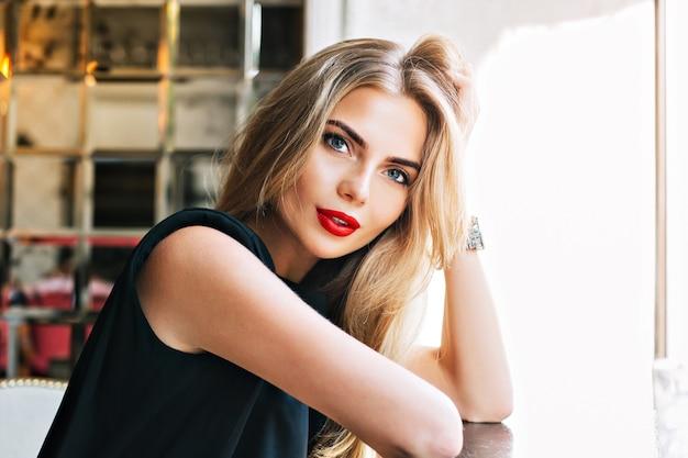 Schöne frau des nahaufnahmeporträts, die auf tisch in der cafeteria lehnt. sie schaut zur kamera.