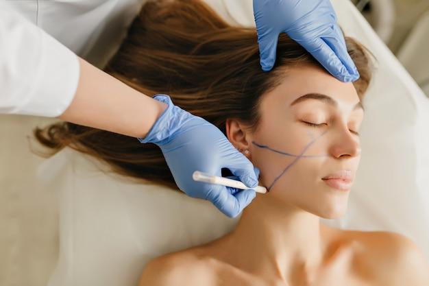 Schöne frau des nahaufnahmeporträts während der kosmetikverfahren, verjüngung im schönheitssalon. dermatologie-verfahren, malen von augenbrauen, hände in blauen schimmern, bei der arbeit, gesundheitswesen, botox