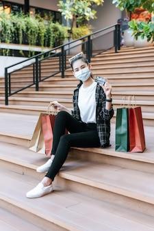 Schöne frau des porträts in der maske, die eine brille auf den kopf hält und die einkaufstasche hält