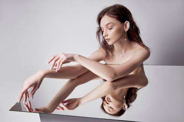 Schöne frau des schönheitsporträts, die auf spiegel liegt. natürliches make-up, schmuckringe an den fingern